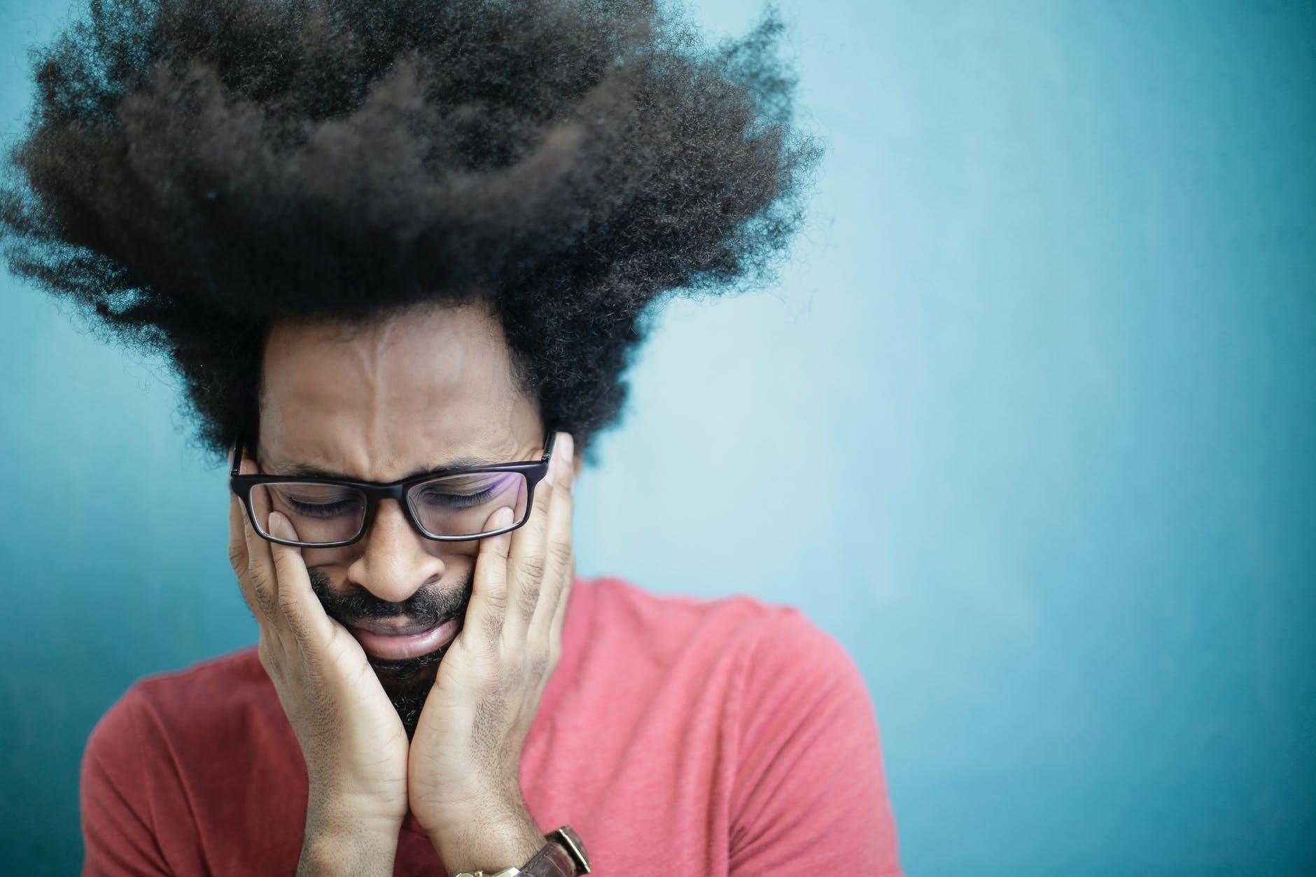 man in red crew neck shirt wearing black framed eyeglasses crying